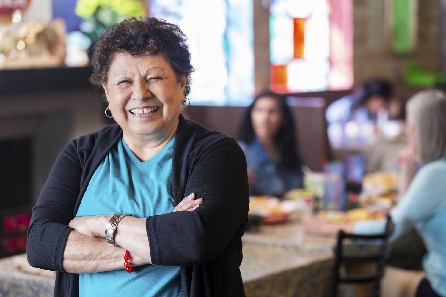 Hispanic grandmother smiling in dining room of family owned restaurant